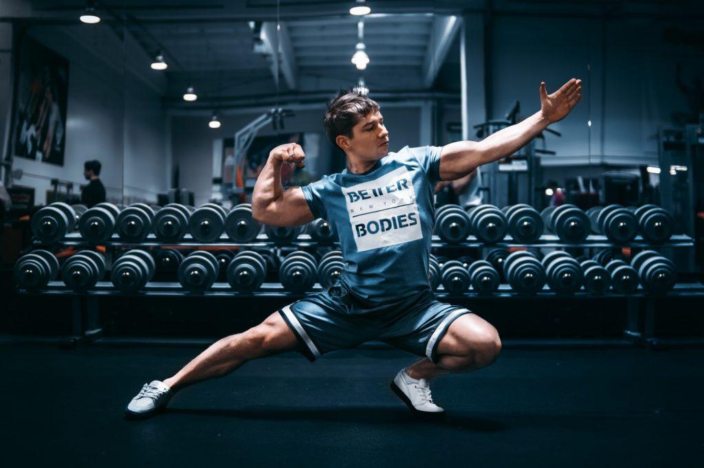 Photographie d'un adepte de la musculation prenant la pose pour montrer ses muscles et ses biceps